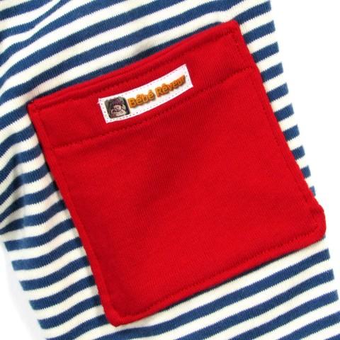 Détail de la poche en jersey rouge sur la maille rayée bleu marine et naturel