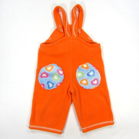 Salopette bébé fille de dos en polaire orange avec 2 gros patchs bleu ciel et petits coeurs colorés sur les fesses